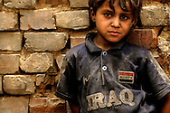 IRAQ, NARWAN - JULY 1: A young boy stands outside his family shelter at the Narwan brick factory, July 1, 2008 in Narwan, Iraq. Twenty miles east of Baghdad, the 170+ small brick factories employ about 30,000 Iraqis, shaping mud into bricks and fire them in kilns burning heavy fuel oil that produces acrid, black smoke visible from satellite imagery 50 miles above the earth's surface. The brick factory employs seasonal workers, many of whom are children - some are as young as four - in highly toxic conditions offering minimal food and water. Respiratory problems are common amongst the workers and children, with no medical personal available to treat them. (Photo by Warrick Page)