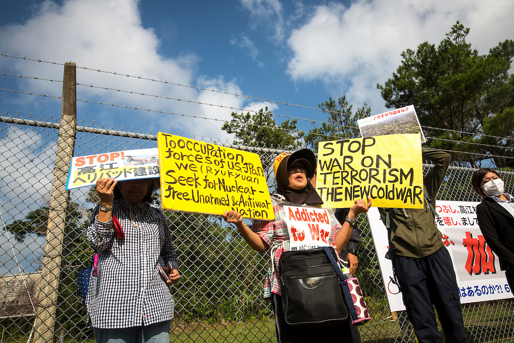 OKINAWA, JAPAN - AUGUST 19 : Anti U.S base protester holding a placards to protest against the construction of helipads in front of the main gate of U.S. military's Northern Training Area in the village of Higashi, Okinawa Prefecture, on August 19, 2016. Japanese government resume construction of total six helipads in a fragile ten million year old Yanbaru forest that is home to endemic endangered species such as the Okinawan rail and Okinawa wood pecker. (Photo by Richard Atrero de Guzman/NURPhoto)