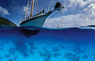 Underwater split level view of ketch in a clear water anchorage in Vava'u, Tonga. South Pacific
