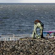 """Nederland Den Oever Zurich 22 november 2008 20081122 Foto: David Rozing ..Serie afsluitdijk. De Afsluitdijk is een belangrijke waterkering en verkeersweg in Nederland. De waterkering sluit het IJsselmeer af van de Waddenzee. Hieraan ontleent de dijk zijn naam. De verkeersweg, onderdeel van Rijksweg a7, verbindt Noord-Holland met Friesland...afsluitdijk ter hoogte van de uitkijktoren. Man bekijkt vanuit auto bronzen beeld Steenzetter.Ter gelegenheid van 50 jaar Afsluitdijk werd in 1982 het beeld de """"Steenzetter"""" van Ineke van Dijk geplaatst. Tekst: """" de strijd tegen het water blijft een strijd door en voor de mens """" standbeeld, monument, mensen, bezoekers,  deltaplan...Foto David Rozing"""
