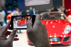 Visitor photographing Ferrari SA Aperta car  with camera phone at Paris Motor Show 2010