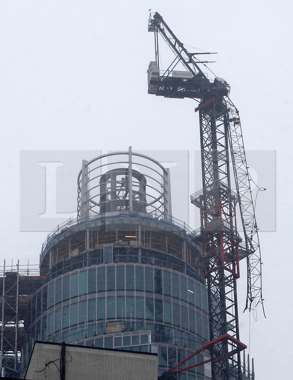 © Licensed to London News Pictures. 18/01/2013. London, U.K..The damaged crane seen hanging from St George's Wharf development near Vauxhall in London today (18/01/13) after a being hit by a helicopter on the morning of the16/01/2012, which then crashed to the ground. HELICOPTER CRASH SITE, VAUXHALL, LONDON, UK  today 18/1/2013. .Photo credit : Rich Bowen/LNP