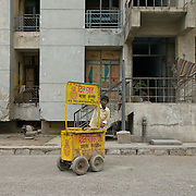 An ice cream (Kulfi) vendor looking for customers among the last inhabitants of a government housing complex in various stages of demolition. Gahziabad, May 2007