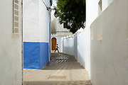 Street architecture and local life, Asilah, Northern Morocco, 2015-08-11.<br /><br />Asilah is a sleepy fishing town in the North of Morocco, just one hour south of Tangier. While not completely off Morocco's well-beaten path, it's often missed by travellers bound inland for Fez or Chefchaouen, yet has a uniquely alluring charm. With an immaculately restored medina that's re-painted vivid shades of blue & white each summer, Asilah has the feel of being Morocco's own Santorini - a great spot to see the more chilled out, seaside town life in Morocco.  <br /><br />The town lies in the middle of a fascinating history in historical, architectural and artistic terms. It's 3,600 year old history that includes a varied range of occupiers, involving Roman, Arab Portuguese, Spanish and French colonisation. Many famous writers and artists have spent time here; in ancient times is it reported Herecules did a tour of the area and, more recently; Paul Bowles, Tennessee Williams, Edith Wharton, Jean Genet (who is buried in the nearby town of Larache), William Burroughs, Jimi Hendrix and Henri Matisse have all found the area inspiring. The Portuguese ramparts remain fully intact and a full day can be spent wandering through its old gates and the ever narrowing medina streets inside the walls.<br /><br />The architecture in Asilah has been heavily influenced by these different periods of occupation, which is one of the main reasons for its unique and characterful feel. Evidence of Mediterranean design can be seen in the rampart walls and gates themselves, reflecting the Spanish & Portuguese influence on the Asilah's development, Roman ruins can be found in the nearby town of Larache and Arab influences are more subtly found in the decorative window shutters and the labyrinth like medina layout to the streets. <br /><br />If a lover of the quirkier details found in the medinas of Morocco, then Asilah won't disappoint, with hundreds of creatively designed doorways, decorative window s