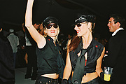 Two women wearing black caps, sunglasses and uniforms, dancing at Posh, Addington Palace, UK, August, 2004