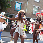 Hackney carnival 2014. The procession started in Ridley Road and passed by the The Hackney Town Hall with thousands of spectators lining the road. A black woman fronts a group of dancers singing to the beats.