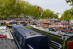 Little Venice, London, April 30th 2017. Narrowboaters from all over the uK gather for the annual Canalway Cavalcade, held on the May Day Bank holiday weekend, organised by the Inland Waterways Association, where boaters get the chance to display their immaculately prepared and brightly painted craft as well as compete in various manoeuvring tests. PICTURED: Narrowboats are moored side by side in Paddington Basin making a cheery display in the lazy sunshine.<br /> Credit: ©Paul Davey<br /> To licence contact: <br /> Mobile: +44 (0) 7966 016 296<br /> Email: paul@pauldaveycreative.co.uk<br /> Twitter: @pauldaveycreate
