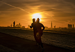 © Licensed to London News Pictures. 30/01/2018. London, UK. Joggers enjoy the sunrise over central London from the top of a frosty Primrose Hill. Photo credit: Peter Macdiarmid/LNP