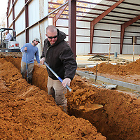 Brent Baker, of New Albany, drops a scoop of dirt into a trench as he volunteers his time to help install the plumbing at Eight Days of Hope new headquarters being built in Pontotoc on Monday morning. Jordan Plumbing in New Albany is donating their time and efforts to get the plumbing done on the project.