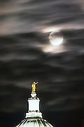 An autumn-harvest moon rises amid wispy clouds in the night sky above the Wisconsin statue atop the dome of the Wisconsin State Capitol in downtown in Madison, Wis., in 1998. (Photo by Jeff Miller - www.jeffmillerphotography.com)