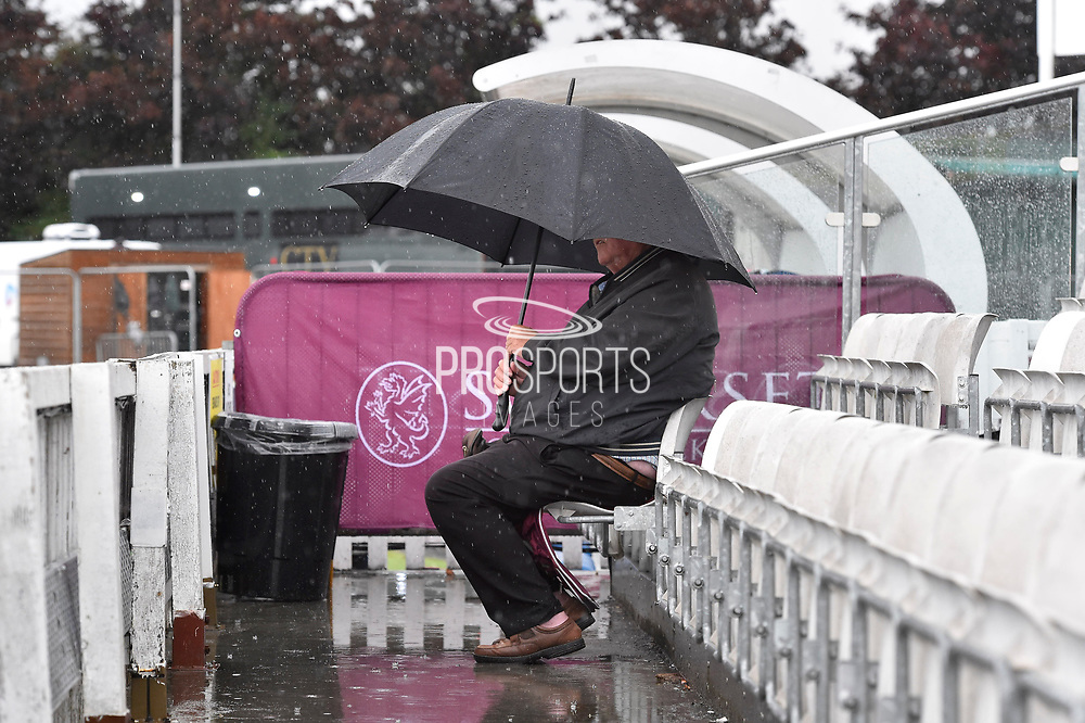 Rain Stops Play - A spectator sits alone in the stands with an umbrella up as the heavy rain continues to fall during the Specsavers County Champ Div 1 match between Somerset County Cricket Club and Essex County Cricket Club at the Cooper Associates County Ground, Taunton, United Kingdom on 23 September 2019.
