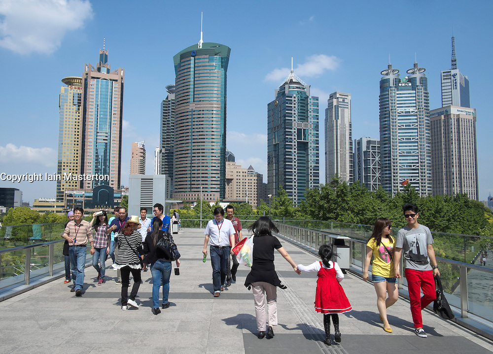 People walking on overhead walkway with skyline of skyscrapers in Lujiazui district of Pudong in Shanghai China