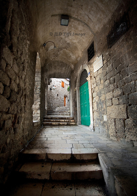 View up a covered walkway along the edge of a town square in front of the cathedral;  Stairs, a closed bright green door, and light at the end of the tunnel.