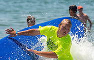 Brett Patro, 13 falls off of his paddle board during the 11th annual 21 Down Beach Day Monday, July 15, 2019 at Schellenger Street beach in Wildwood, New Jersey. Every summer, the Wildwood Beach Patrol opens Lincoln Ave Beach for kids with down syndrome and their families for 21 Down Beach Day. Often, kids with down syndrome aren't comfortable in the ocean. Their parents can't just relax and watch them frolic. But on July 15th, the kids swim with seasoned Wildwood lifeguards on soft-top paddle boards. (Photo by William Thomas Cain / CAIN IMAGES)