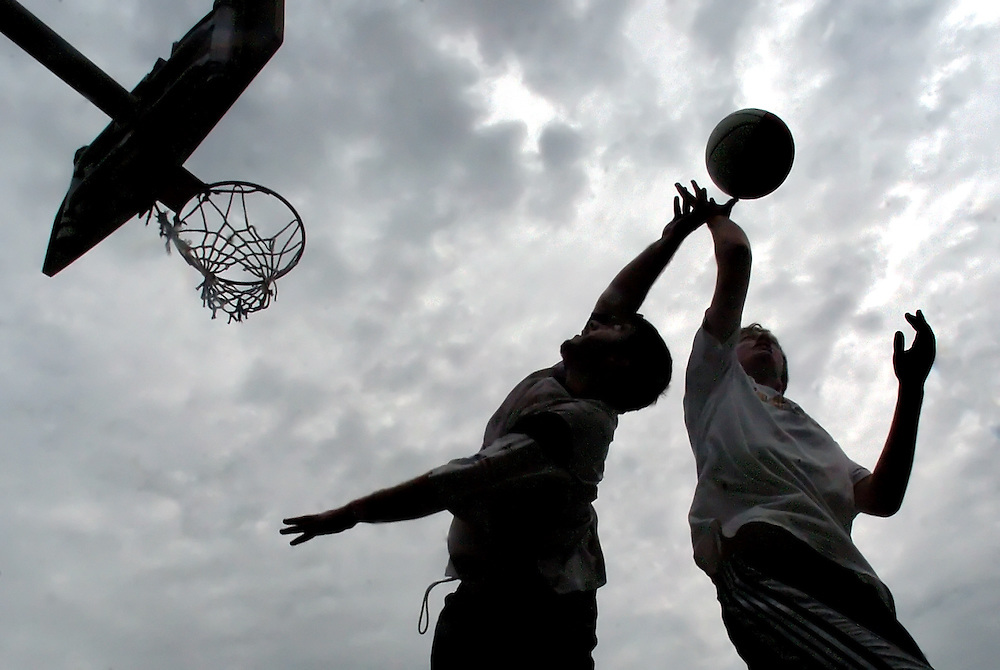 Rockport: Kirk Saccardo, 18, far right, and Keith Lee, 19, both of Rockport,  reach for a rebound while playing a game of two-on-two basketball in the parking lot of Rockport High School Tuesday afternoon. Also playing were Taylor Haselgard, 17, of Lanesville, and Aubree Giarrosso, 18, of Rockport..Photo by Mike Dean/Gloucester Daily Times Tuesday, June 12, 2007