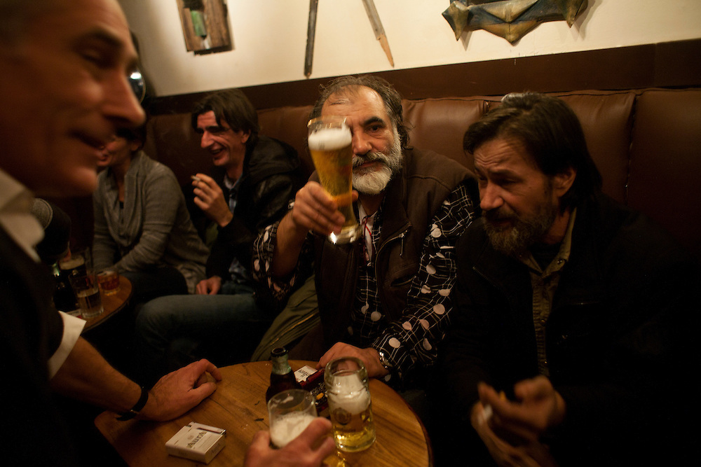 Bosnian artist Jusuf Hadzifejzovic and his friends hold court at the Underground bar in Sarajevo, a popular hangout with artists and writers. Hadzifejzovic is an elder statesman and a well-known, internationally recognized artist in his own right with many exhibitions and performances in Italy. Many of his themes deal with the struggle of post-Yugoslavia identity. He is perhaps single-handedly responsible for one of the most interesting recent developments in the Sarajevo scene: engineering new galleries and ateliers for many modern artists in a half-empty communist era shopping center located in the basement of a sporting center that was part of the 1984 Olympics, called Skenderija. He is at the center of a group of young artists who he mentors.