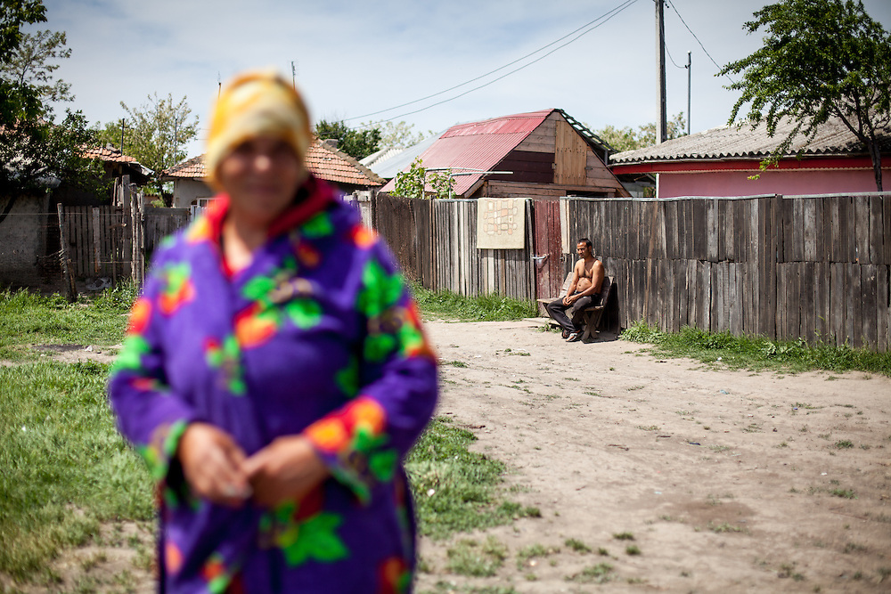 A woman walking the streets with her bathrobe and a sun bathing man in the Roma area of Frumusani.