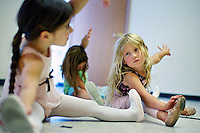 Allie Van Ditto, 3, stretches with her class before working on her dance moves Friday at Expressions School of Performing Arts in Post Falls. Expressions School of Performing Arts is moving to a larger facility in September that will have four dance floors and five music studios.