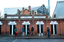 LONDON, ENGLAND - Wednesday, February 12, 2014: A man walks his dog past the turnstiles at Fulham's Craven Cottage stadium before the Premiership match between Fulham and Liverpool. (Pic by David Rawcliffe/Propaganda)
