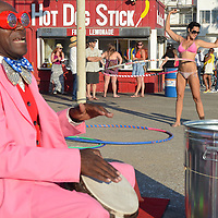 A girl hula hoops while Lenny Hoops lays down the beat at Ocean Front Walk on Sunday, July 20, 2014.