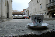 Close up of coffee cup, with old town buildings in background. Trogir, Croatia