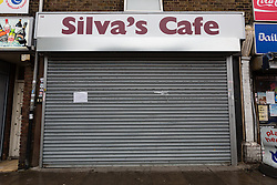 © Licensed to London News Pictures. 24/09/2014. Edmonton, UK. Silva's cafe in Church Street, Edmonton is closed today and a notice posted on the shutter notifying customers of Palmira Silva's funeral which takes place today in Edmonton, London. Palmira Silva, a grandmother who was killed by a machete in her back garden used to work at Silva's Cafe. Photo credit : Vickie Flores/LNP