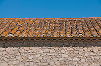 Rustic Provence stone building and tiled roof with blue sky background,