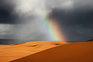 Sahara desert sand dunes with rainbow against dark, cloudy, rainy sky at Erg Chebbi, Merzouga, Sahara desert of Morocco.