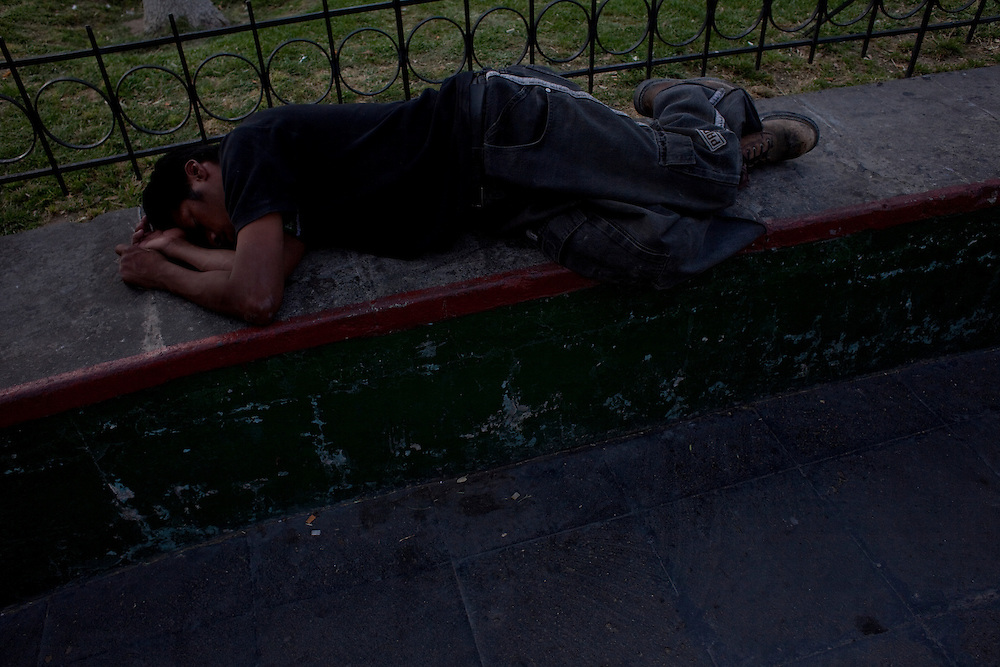 A young man sleeps in a park in the city center  in Ciudad Juarez, Chihuahua on May 12, 2010.
