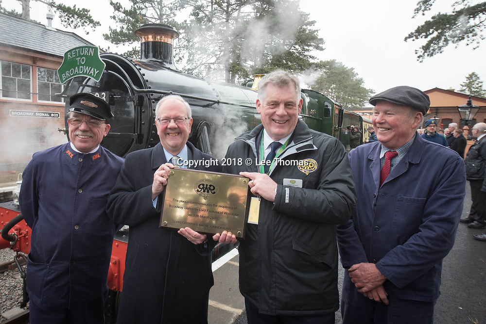 Broadway Station, Broadway, Worcestershire, UK. 30th March 2018.  A steam train carry members of the public departed from Broadway Station in the Cotswolds for the first time in almost 60 years today. On Good Friday, Lord Richard Faulkner of Worcester formally opened the station and traveled on the footplate of Great Western Railway-designed engine no.7903 'Foremarke Hall', the first public train to Cheltenham for 58 years. The new station has been built by GWSR volunteers to a similar design as the 1903 original station. Most of the stations on the former Stratford-upon-Avon to Cheltenham line were closed by British Railways in 1960 and the railway closed completely in 1976, with track and infrastructure removed by 1979. Pictured: Lord Richard Faulkner (second from left) holds a plaque in front of the engine. // Lee Thomas, Tel. 07784142973. Email: leepthomas@gmail.com  www.leept.co.uk (0000635435)