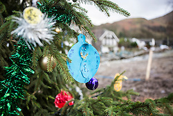 © Licensed to London News Pictures. 23/12/2015. Glenridding UK. The defiant residents of Glenridding that flooded twice have now put up a Christmas tree on the banks of the beck despite more weather warnings being issued by the met office warning of 80mph winds as Storm Eva approaches. Photo credit: Andrew McCaren/LNP