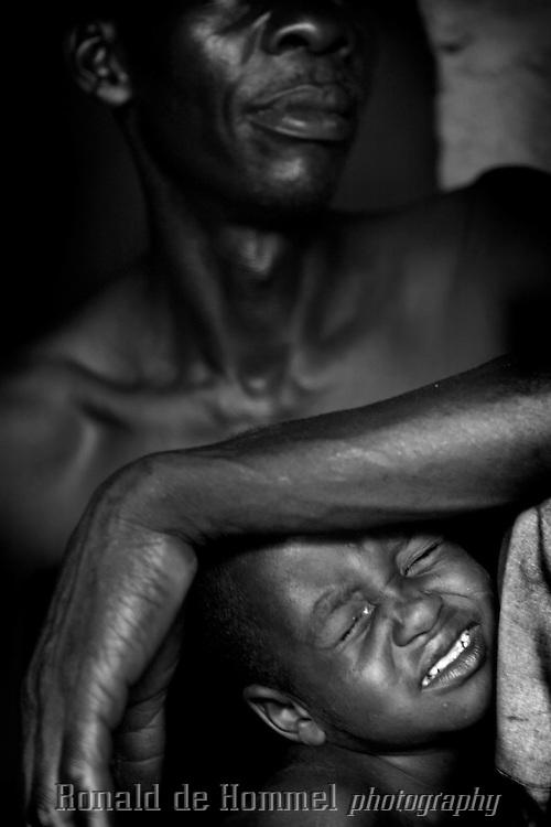 Father and son in a small hut north east of Paoua..Right in the heart of Africa, surrounded by Chad, Sudan and the Democratic Republic of Congo is the Central African Republic (CAR). In line with its neighbours this country is ravaged by internal conflicts. Several rebel groups are engaged in a permanent war with the government. Army and militias have burnt down thousands of villages. The population fled into the bush where an estimated 100,000 still live. ..The Central African Republic has many Internally Displaced People (IDP's). Nobody knows how many. It is almost impossible to register them. There is only one IDP camp in a country the size of Texas. Many crossed the border to Chad, but the majority lives spread out in the bush. Whole communities live in small huts trying to hide amongst the barren trees. Small patches of land are cultivated but don't produce enough to feed the population. The main crop is Cassava. The shortage of food and the unbalanced diet result in children with swollen belies, malnourished babies and a rate of death amongst children under the age of five which, at 167 out of 1000, is one of the highest in the world. ...---.Vader en zoon in hun hutje ten noord oosten van Paoua..Omringd door Chad, Darfur en de Democratische Republiek Congo ligt de Centraal Afrikaanse Republiek. In lijn met de buren wordt ook dit land verscheurd door interne conflicten. Verschillende rebellengroepen zijn in een permanente oorlog met de regering verwikkeld. Duizenden dorpen zijn door, vooral het leger, maar ook door andere milities afgebrand. De bevolking is gevlucht..Het enige verschil is dat de wereld hier niet in gei?nteresseerd lijkt. Het is een van de armste landen ter wereld, de economie ligt al decennia op zijn gat en zelfs de meeste hulporganisaties lopen met een grote boog om het land heen. ..De Centraal Afrikaanse Republiek (CAR) telt een hoog aantal interne vluchtelingen. Niemand weet hoeveel want vluchtelingen worden niet geregistreerd. Er is maar e?