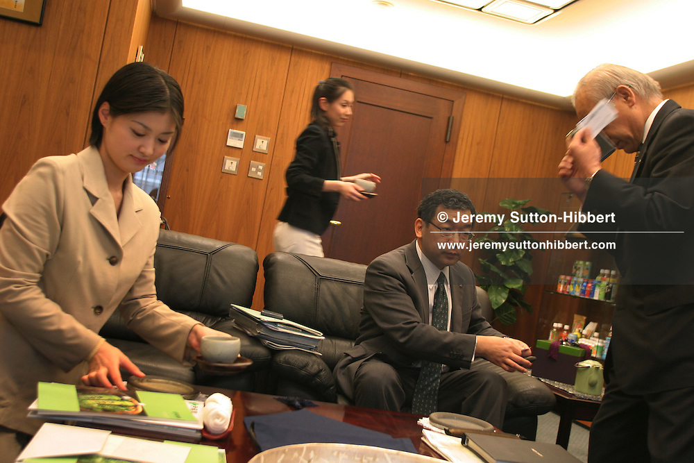 Female employees places cups of tea on tables in the boardroom whilst general managers of ItoEn Ltd. ( a large tea company),prepare for an interview, in Tokyo, Japan, on Thursday, Apr. 27th 2006. During interviews it is common for female assistants to enter the rooms silently , bringing refreshment drinks of green tea, coffee, or orange juice, to the company head and his guests.