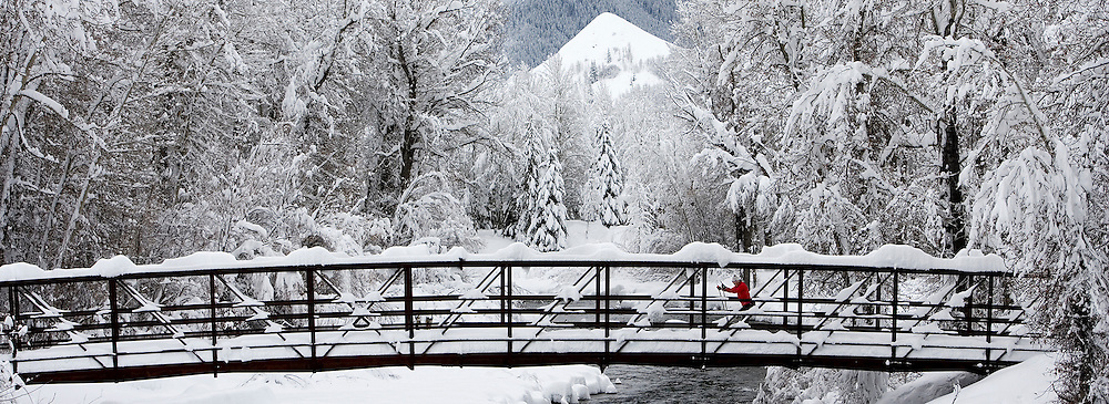 Skier in red crosses over the Lake Creek Trail Head Bridge on cross country skis on  a super snowy day in the Sun Valley, Idaho area