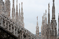 Milan, Italy, Duomo Cathedral. Forest of ornate spires springing up from the roof with intricate stone details in the foreground.