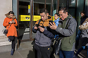 Asian tourists struggle with smartphone technology while outside Selfridges on Oxford Street on a bright day in central London.