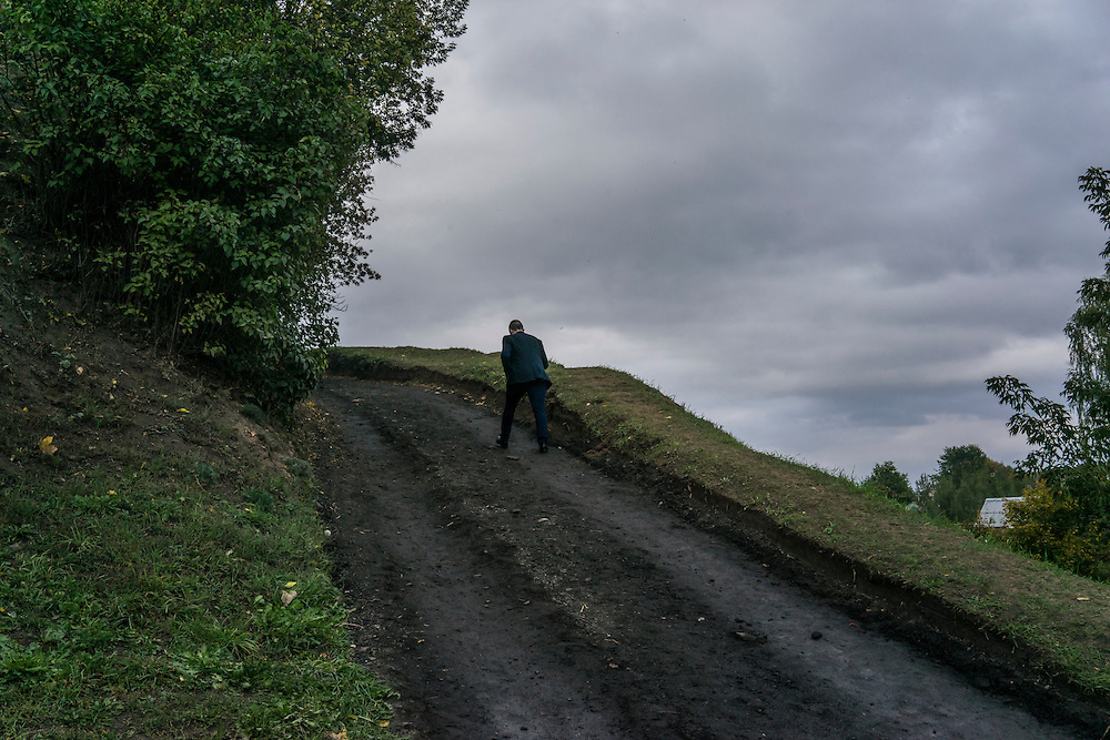 A man walks up a dirt road on Saturday, September 24, 2016 in Mstislavl, Belarus.