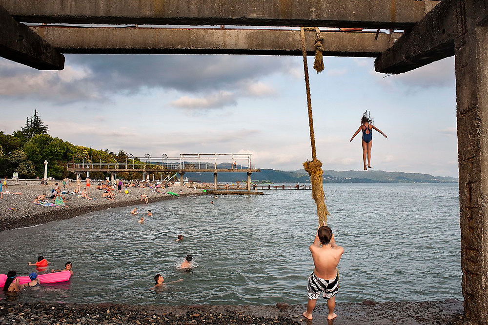A girl jumps into the sea from the remnants of a concrete structure built by the shore, Sukhumi beach, Abkhazia