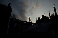 A man stands on wreckage in the hilltop neighborhood of Fort National in Port-au-Prince, Haiti, Sunday, February 28, 2010.  The neighborhood was one of the hardest hit in the city and still has not received even the most basic of services, including food, water or tents.