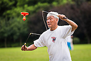 An elderly man performs spinning top exercise in Fuxing Park Shanghai, China