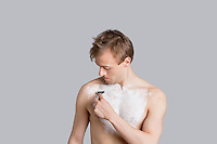 Young man shaving chest with razor over colored background