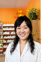 Portrait of a happy Asian employee in drugstore
