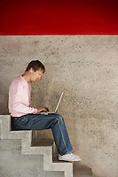 Man Using Laptop on Stairway