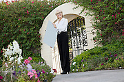 Portrait of a senior female real estate agent holding sign board in front of entrance gate