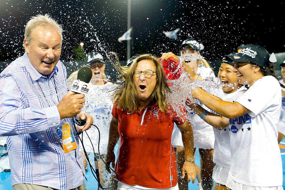 Stanford players dump water over head coach Lele Forood's head as she gives an interview to Dave Kozlowski during the NCAA women's team tennis championship at the Khan Outdoor Tennis Complex Tuesday, May 21, 2013 on the University of Illinois campus in Urbana, Ill.