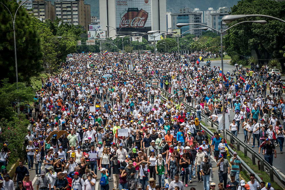 CARACAS, VENEZUELA - May 10, 2017: The streets of Caracas and other cities across Venezuela have been filled with tens of thousands of demonstrators for nearly 100 days of massive protests, held since April 1st. Protesters are enraged at the government for becoming an increasingly repressive, authoritarian regime that has delayed elections, used armed government loyalist to threaten dissidents, called for the Constitution to be re-written to favor them, jailed and tortured protesters and members of the political opposition, and whose corruption and failed economic policy has caused the current economic crisis that has led to widespread food and medicine shortages across the country.  Independent local media report nearly 100 people have been killed during protests and protest-related riots and looting.  The government currently only officially reports 75 deaths.  Over 2,000 people have been injured, and over 3,000 protesters have been detained by authorities.  PHOTO: Meridith Kohut