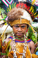 Young girl wearing traditional tribal dress including animals skins and colourful feathers at the Goroka show in the Papua New Guinea highlands.