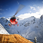 A helicopter lands on an alpine drill pad in southwest British Columbia