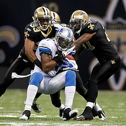January 7, 2012; New Orleans, LA, USA; New Orleans Saints cornerback Jabari Greer (33) and safety Malcolm Jenkins (27) tackle Detroit Lions wide receiver Calvin Johnson (81) during the 2011 NFC wild card playoff game at the Mercedes-Benz Superdome. Mandatory Credit: Derick E. Hingle-US PRESSWIRE