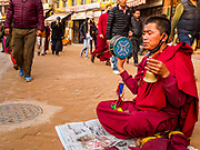 17 MARCH 2017 - KATHMANDU, NEPAL: A Buddhist monk prays during morning payers in front of Boudhanath Stupa in Kathmandu. The stupa is the holiest site in Nepali Buddhism. It is also the center of the Tibetan exile community in Kathmandu. The Stupa was badly damaged in the 2015 earthquake but was one of the first buildings renovated.         PHOTO BY JACK KURTZ